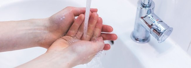 Hands being washed under running tap